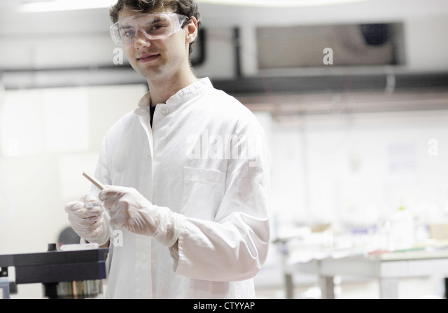 Scientist holding dropper in lab - Stock Image