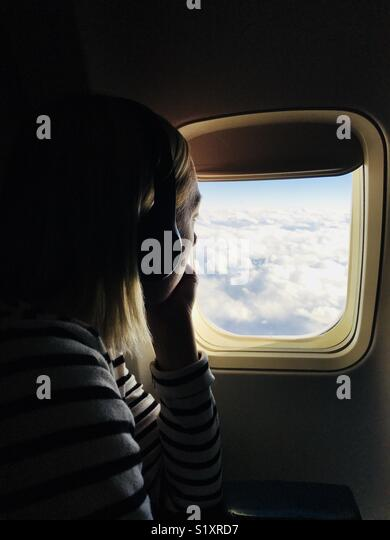A woman looking out an airplane window. - Stock Image