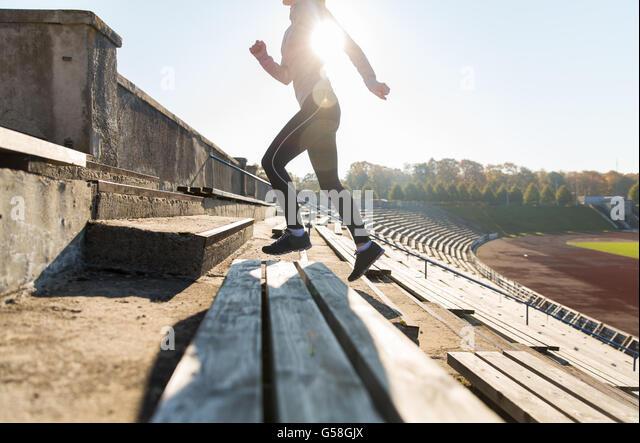 close up of woman running upstairs on stadium - Stock-Bilder