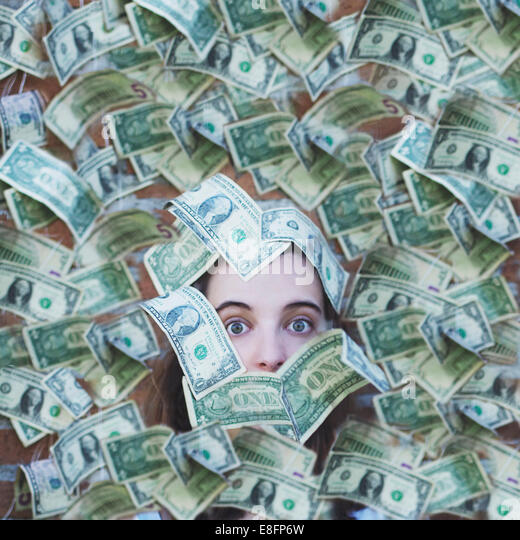 Portrait of a woman covered in American dollar bills - Stock-Bilder