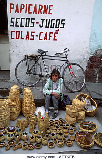 Ecuador Saquisili Market Otavalo Cotopaxi Chibuleos Indigenous natives teen female vendor baskets ceramics bicycle - Stock Image