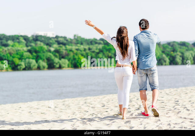 Couple holding hands and walking on a sandy beach - Stock-Bilder