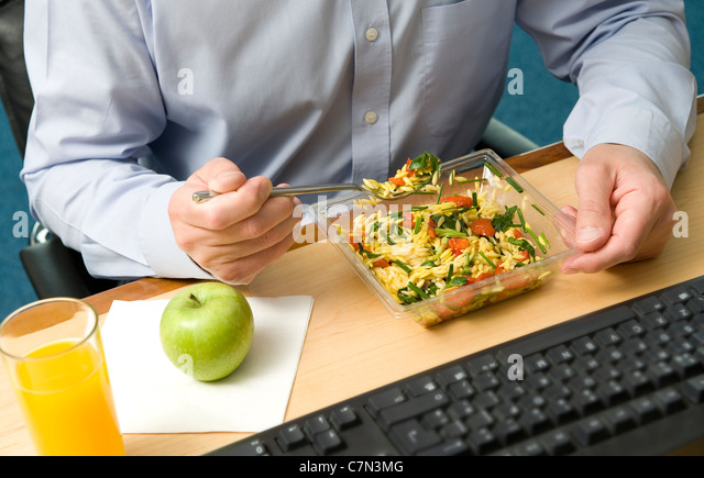 male office worker eating working lunch - Stock-Bilder