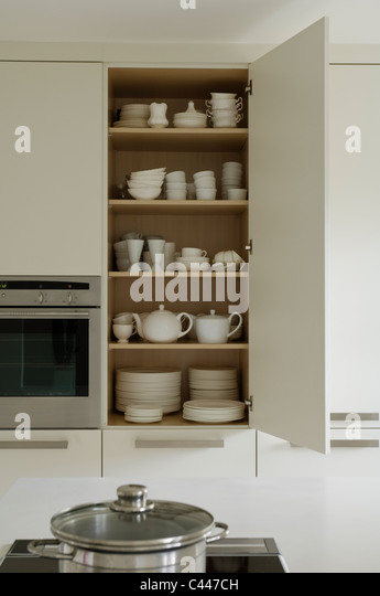 Open crockery cupboard in white contemporary kitchen - Stock Image