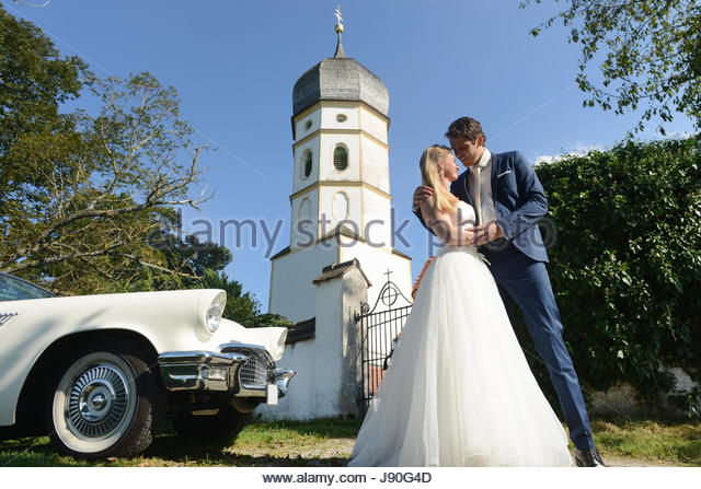Bride And Groom Outside Church With Car On Wedding Day - Stock-Bilder
