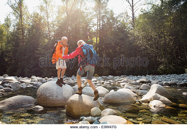 Couple crossing rocks over creek in woods - Stock Image
