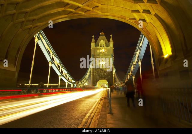 Traffic trails through Tower Bridge, London, at night - Stock Image