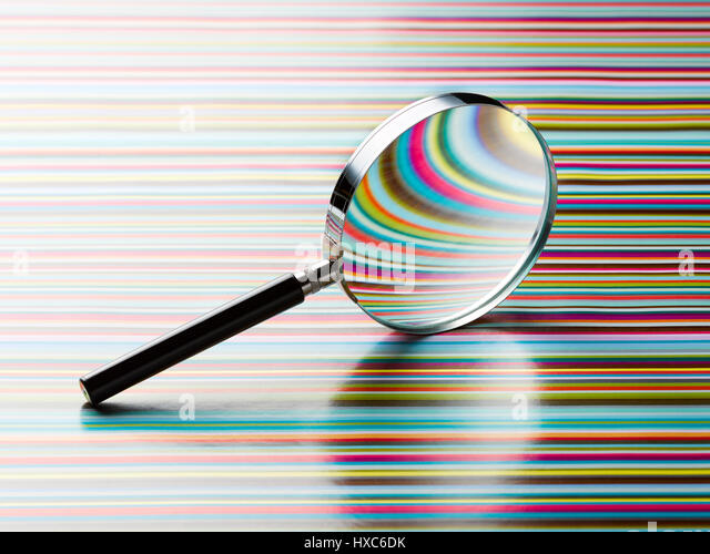 Magnifying glass leaning on striped background - Stock Image