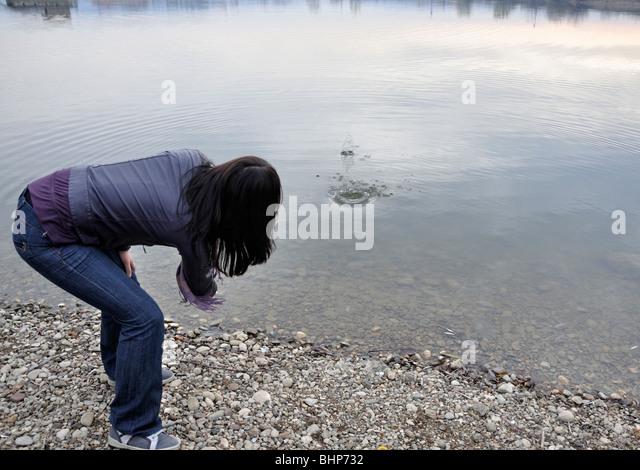 Woman skipping stone in lake - Stock Image