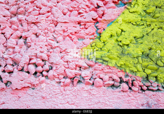 pink and yellow coat on the concrete wall - detail - Stock Image