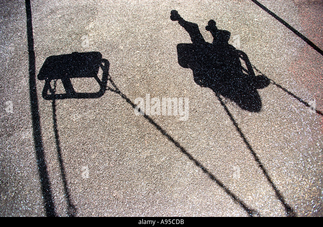 The shadow of a young girl or boy playing on a swing - Stock-Bilder