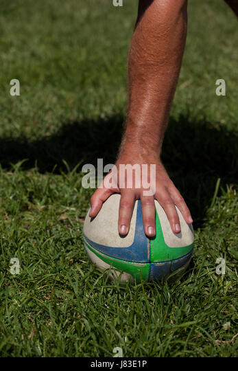Cropped hand touching rugby ball on grassy field - Stock Image