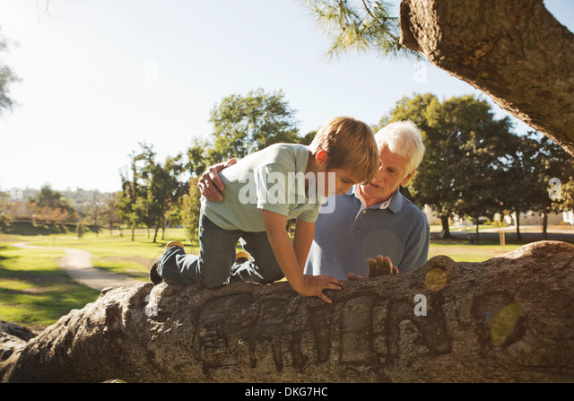 Grandfather helping grandson to climb tree - Stock Image
