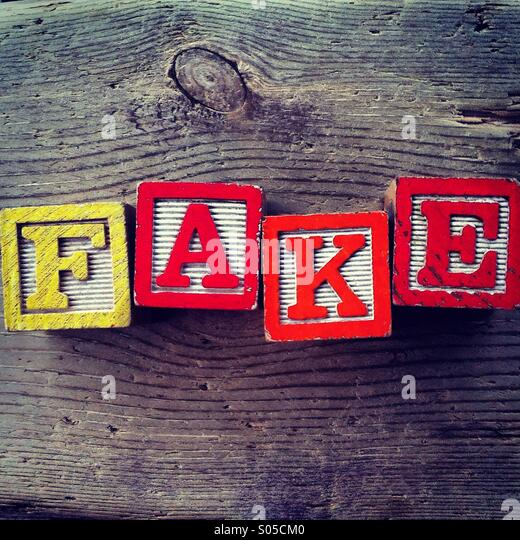 It's a photo of few wood blocks with colored letters on them that are combined together to create the word FAKE - Stock Image