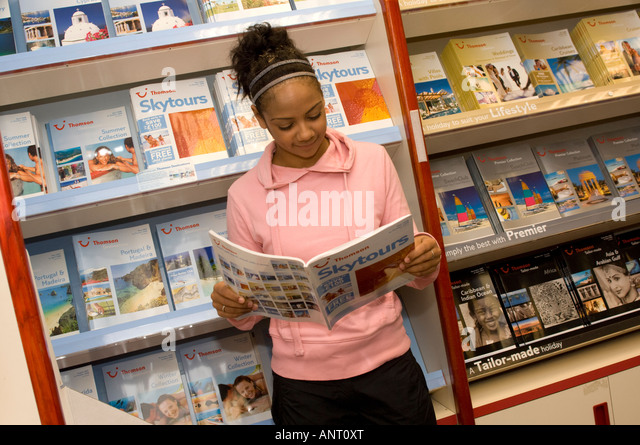 dark skinned black young woman looking at travel brochure in Thomas Cook travel agent, planning annual foreign holiday - Stock Image