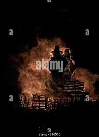 Cardboard silhouette of Guy Fawkes on top of a burning bonfire - Stock-Bilder