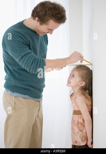 Father measuring daughter s height on wall - Stock Image