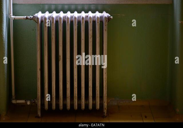 Old metallic water heater radiator mounted on a green wall - Stock Image