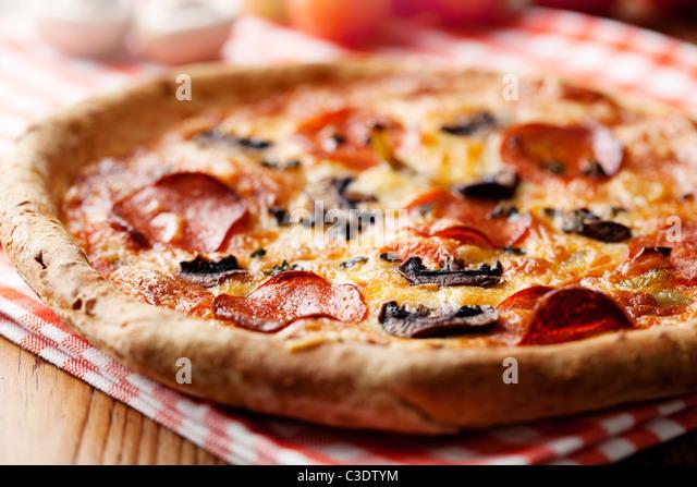 pepperoni and mushrooom pizza closeup, shallow dof - Stock Image