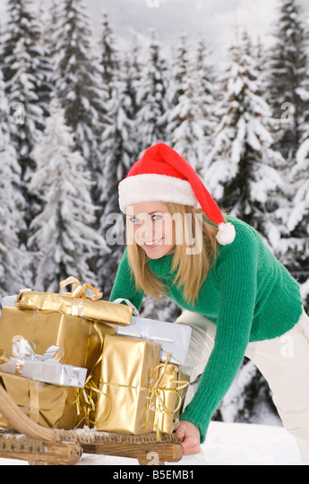 Austria, Salzburger Land, Altenmarkt, young woman pushing sledge brimming with Christmas presents - Stock Image