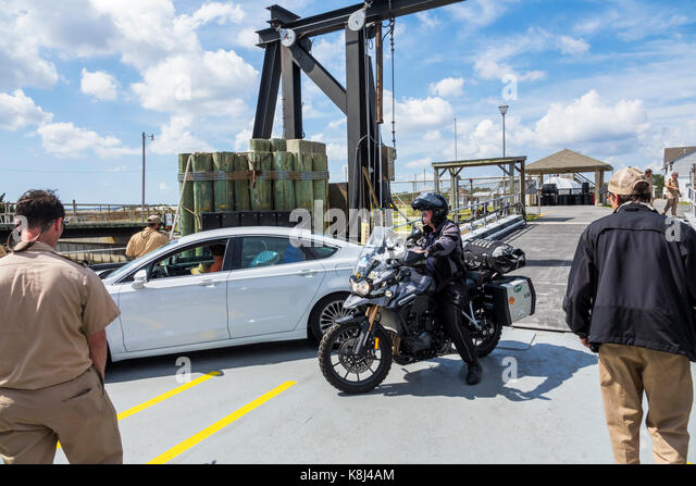 North Carolina NC Cedar Island Outer Banks Pamlico Sound Ferry Terminal slip man crew ramp loading vehicle car motorcycle - Stock Image
