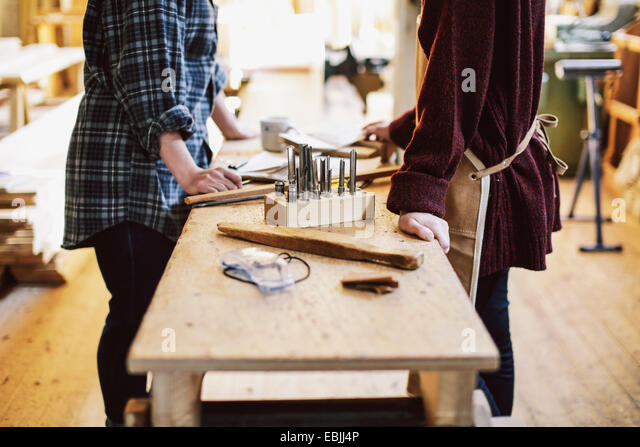 Cropped view of two craftswomen at workbench in pipe organ workshop - Stock Image