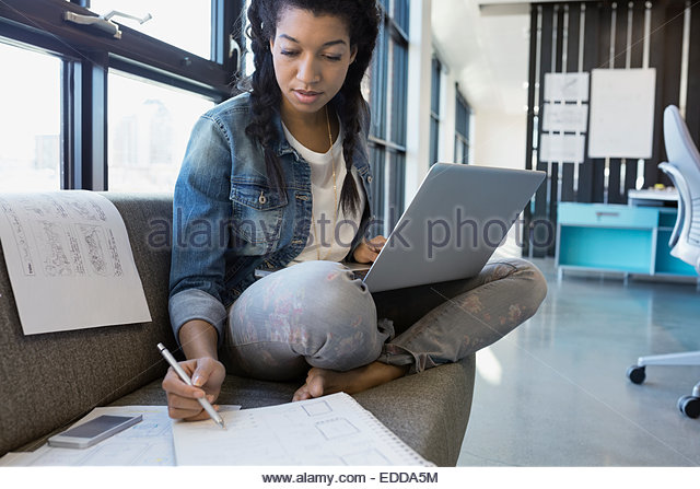 Designer working at laptop on sofa in office - Stock Image