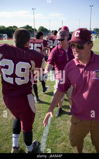 At game end footballers shake hands with their coaches - Stock Image