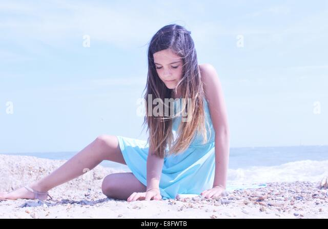 Girl sitting on beach - Stock Image