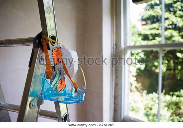 Protective safety goggles and dust mask hanging from step ladder in room beside window - Stock Image