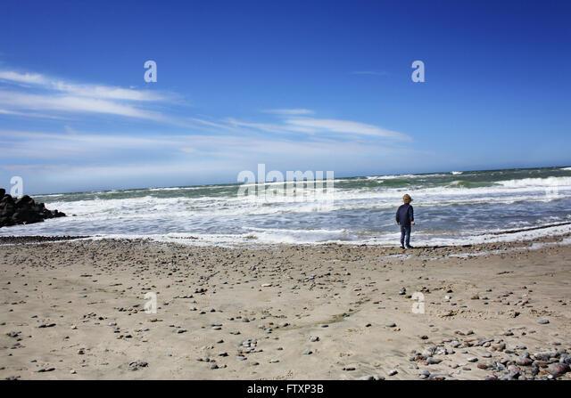 Boy walking along the beach, Denmark - Stock Image