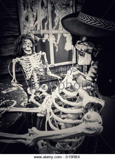Two Skeletons on Chairs in  conversational Pose - Stock Image