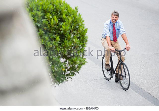 High angle view of mature businessman cycling in city - Stock Image