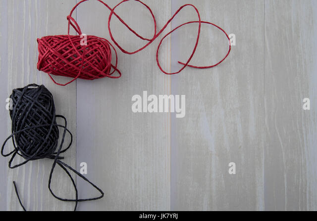 Red and Black Twine on Light Wooden Background - Stock Image