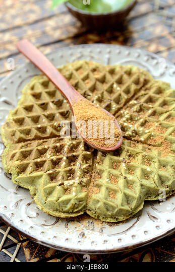 Homemade waffles with addition of matcha, pistachios, flax seeds. Decorated with coconut sugar. - Stock Image