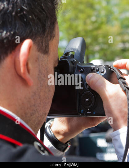 Man looking through viewfinder of dSLR camera - USA - Stock Image