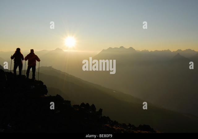Two Hikers on Glanderspitze looking at Krahberg and Lechtaler Alpen range, Venet, Oetztaler Alpen range, Tyrol, - Stock Image
