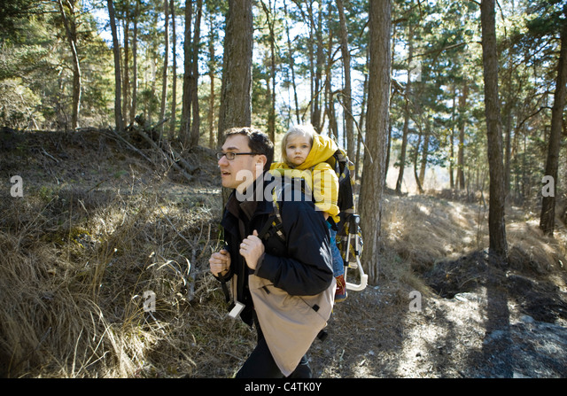 Father hiking in woods with baby daughter in backpack carrier - Stock Image