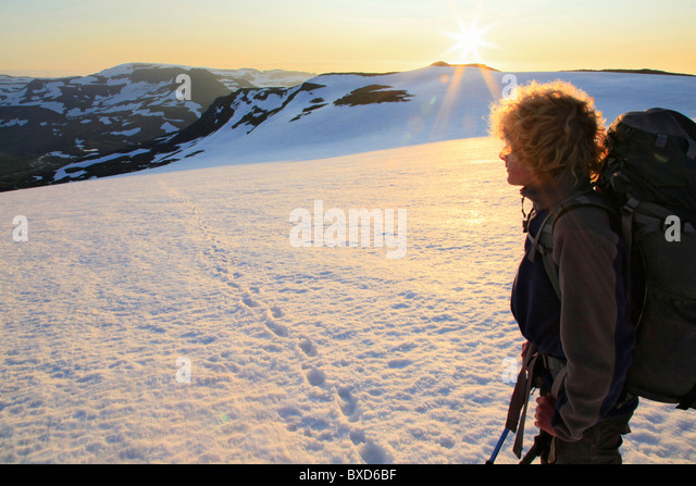 Backpacker looking back at sunrise while crossing Drangajökull ice cap, Hornstrandir Peninsula, Iceland - Stock Image