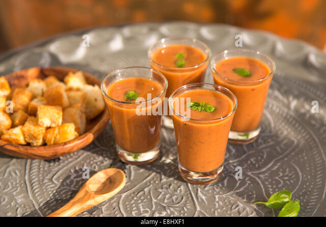 outdoors shot of tomato gazpacho or soup in glasses with basil on metal tray - Stock Image