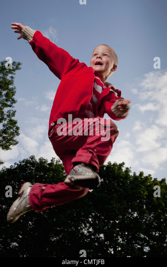Low angle view of boy (6-7) jumping - Stock Image