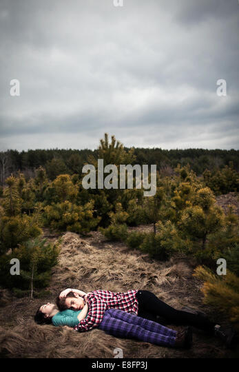 Teenagers (14-15) lying on ground and embracing - Stock-Bilder