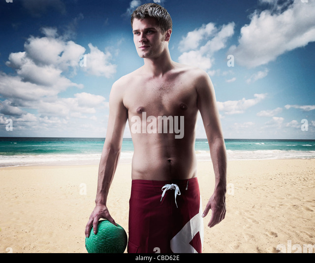 Man holding volleyball on beach - Stock Image
