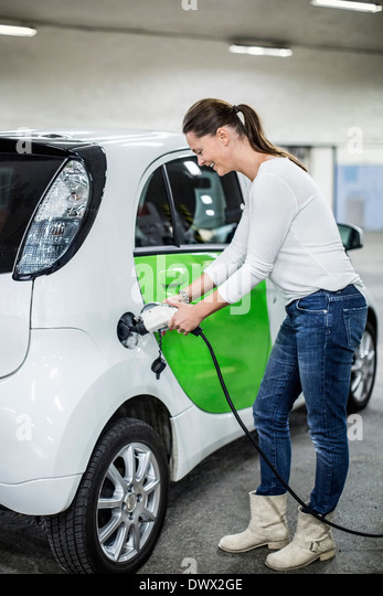 Full length of woman charging electric car at gas station - Stock Image