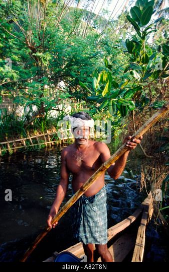 India Kerala indian man with boat in backwaters - Stock Image