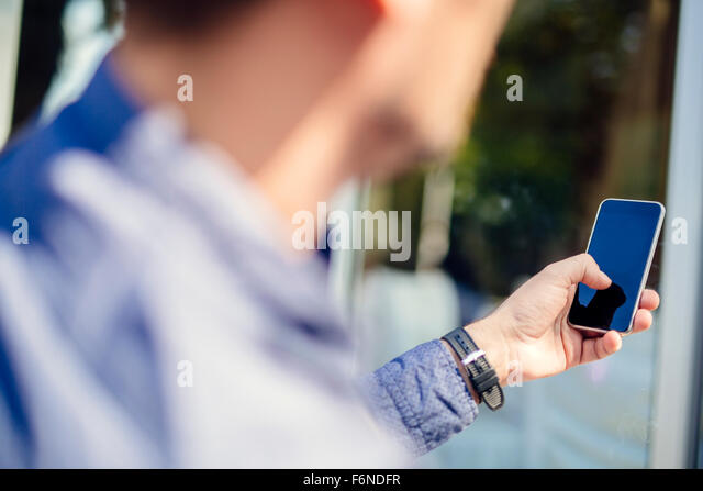 Man holding phone outdoors and tapping it - Stock-Bilder