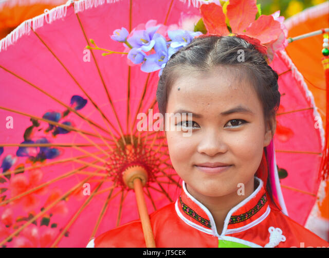 Smiling Thai Chinese Girl in Traditional Dress with Red Parasol (IV), Northern Thailand. - Stock Image