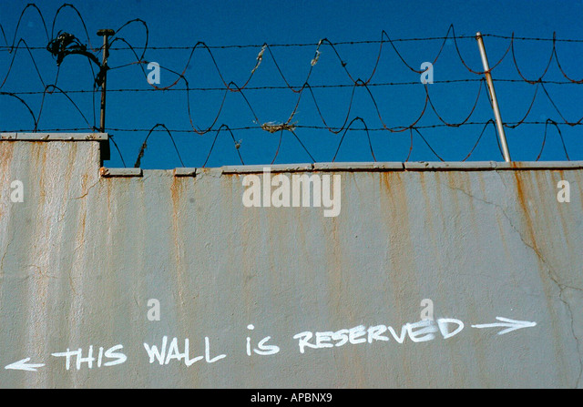 Urban Scene of Razor Wire and Graffiti This Wall is Reserved in New York City Copy Space - Stock Image