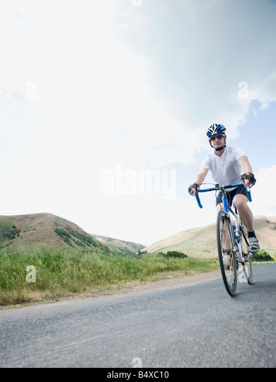 Cyclist on country road - Stock Image