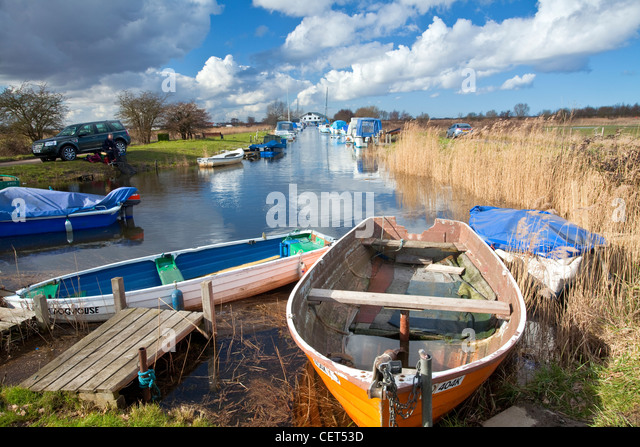 An angler fishing at Martham Staithe on the Norfolk Broads. - Stock Image